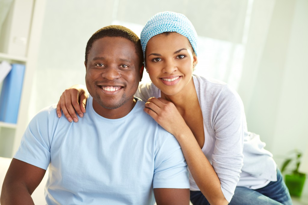 Image of young African couple looking at camera with smiles